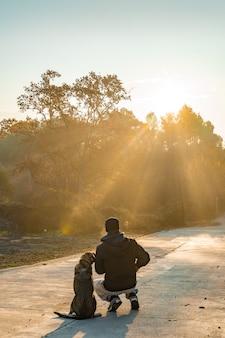 Молодой человек развлекается со своей собакой на природе с лучами утреннего солнца, люблю свою собаку