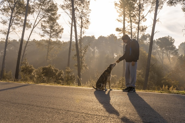 Young man having fun with his dog in nature with the rays of the morning sun warm glow