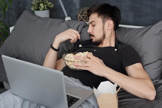 ベッドの上にラップトップを持って横たわっていて、tシャツからポップコーンを食べている彼のいたるところにポップコーンを持っている若い男