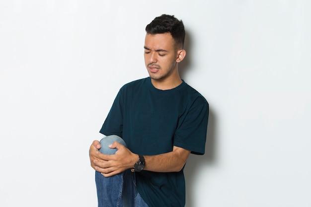 白い背景で隔離の膝の痛みを持つ若い男