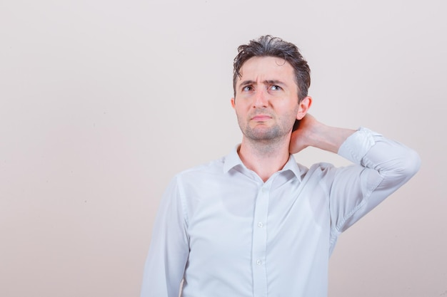 白いシャツに首の痛みがあり、不快に見える若い男