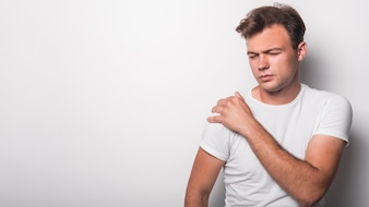 Young man having pain in shoulder against white background