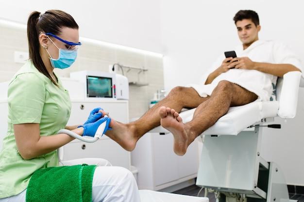 Молодой человек, имеющий лечение педикюром в современном салоне красоты.