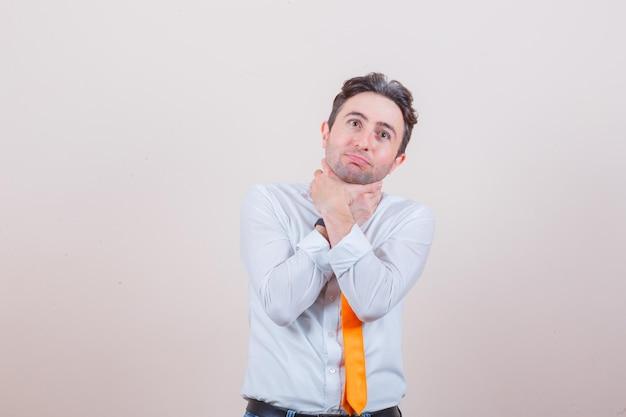 シャツに喉の痛み、ネクタイ、体調不良の若い男