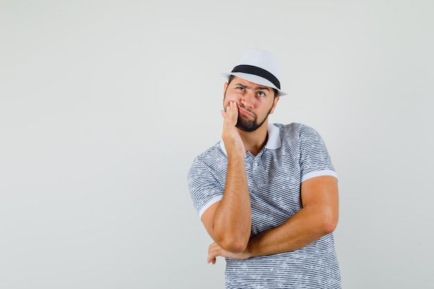 Tシャツ、帽子、不快に見える歯痛を持っている若い男。正面図。
