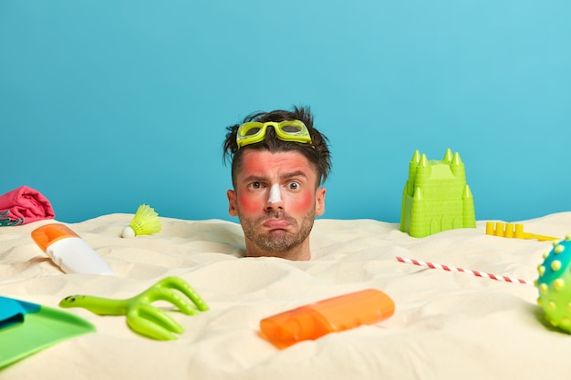 Young man head with sunscreen cream on face surrounded by beach accessories