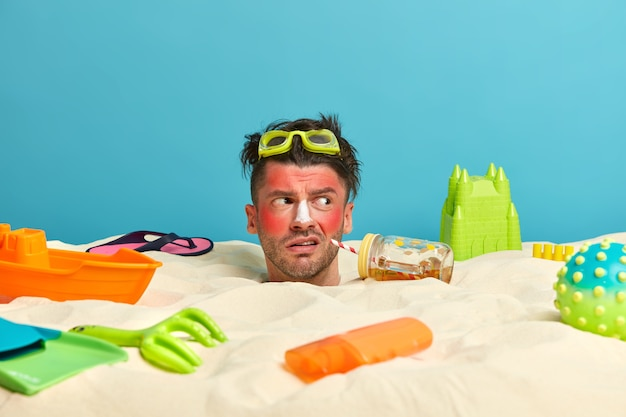 Testa di giovane uomo con crema solare sul viso circondato da accessori da spiaggia