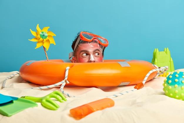 해변 액세서리로 둘러싸인 얼굴에 선 스크린 크림으로 젊은 남자 머리