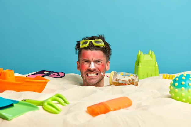 Голова молодого человека с солнцезащитным кремом на лице в окружении пляжных аксессуаров