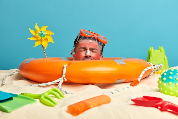 Голова молодого человека с солнцезащитным кремом на лице в окружении пляжных аксессуаров Бесплатные Фотографии