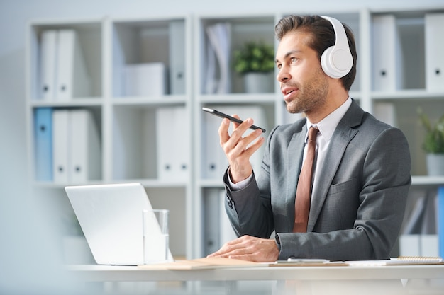 Young man in headphones and elegant suit holding smartphone in front of himself while speaking