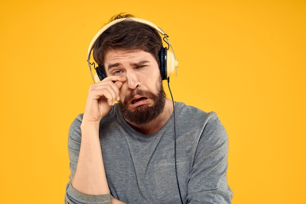 Young man in headphones in hands posing emotionally