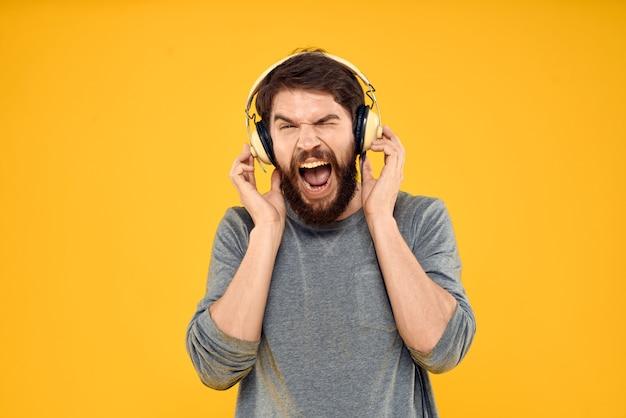 Young man in headphones in hands posing emotionally