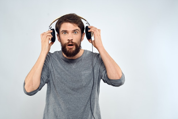 Young man in headphones listening to music isolated