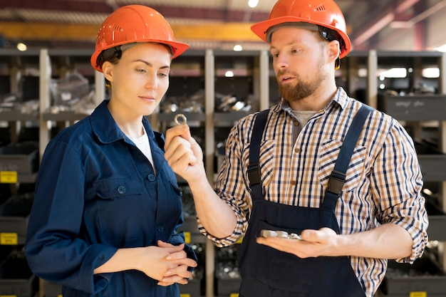 Young man in helmet and overalls showing his colleague one of spare parts while describing its qualities
