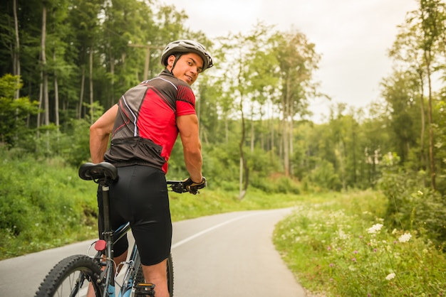 Young man in helmet riding on mountain bicycle.