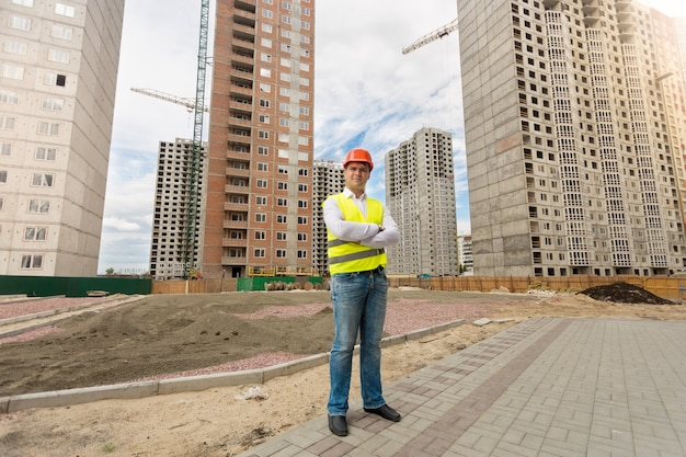 Young man in helmet and safety vest standing on building site