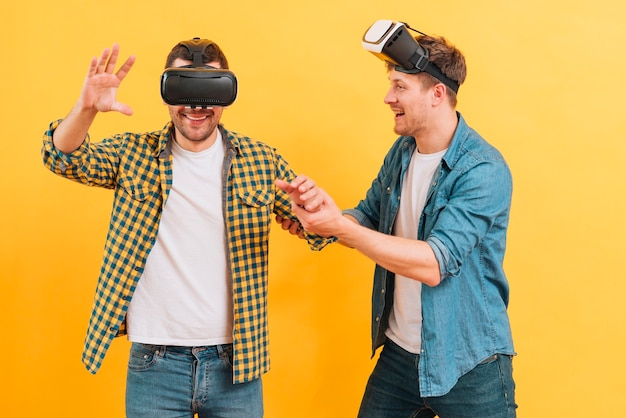 Young man helping his friend wearing glasses of virtual reality against yellow background