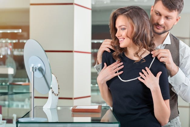 Young man helping his girlfriend with fitting necklace at the je