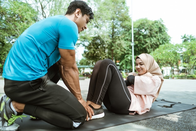 A young man helps hold the legs of a veiled girl doing sit ups while exercising outdoors in the park