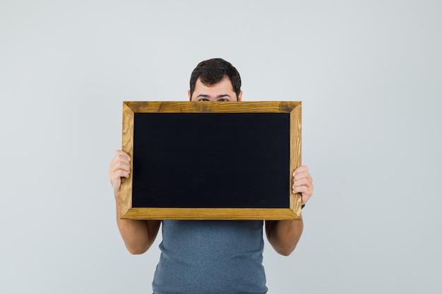 회색 티셔츠에 칠판 뒤에 얼굴을 숨기고 젊은 남자