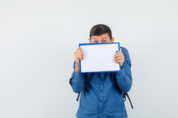 파란색 셔츠에 클립보드 뒤에 얼굴을 숨기고 무서워 보이는 젊은 남자, 전면 보기.