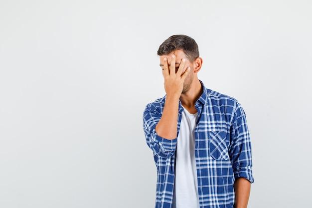 Giovane uomo che nasconde il viso dietro la mano in camicia e guardando sconvolto, vista frontale.