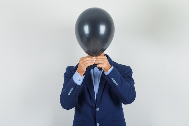 Young man hiding face behind black balloon in suit