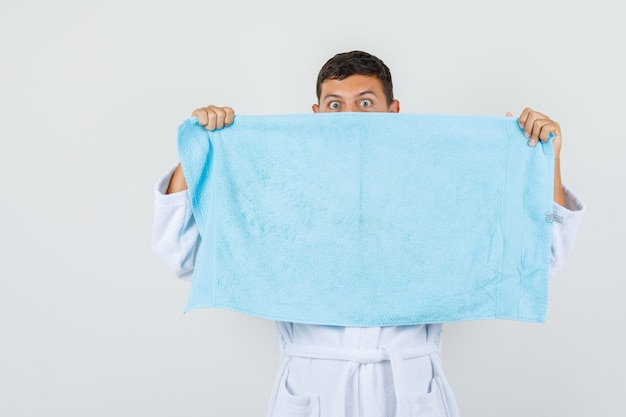 Young man hiding face behind towel in white bathrobe and looking scared , front view.