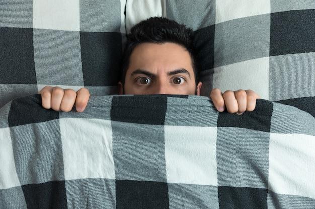 Молодой человек прячется в постели под одеялом у себя дома.