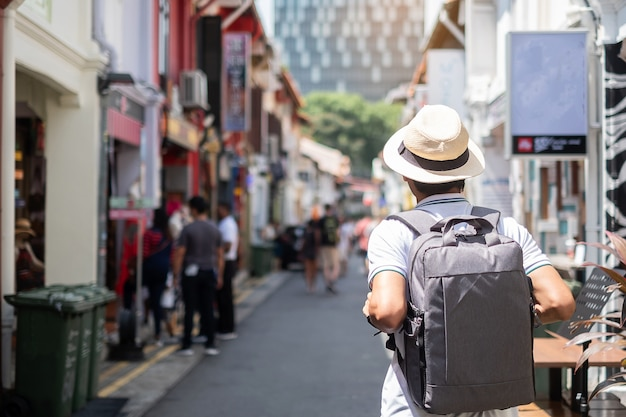 Young man hipster traveling with backpack and hat