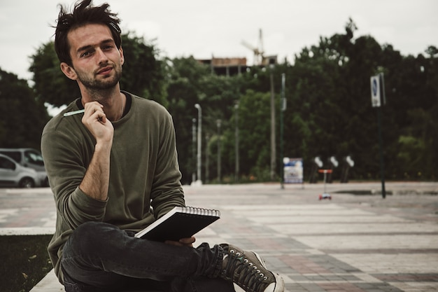 Young man hipster writing in notebook on street, side view.