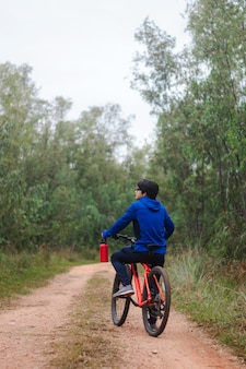 Young man on his bike on a forest road, playing sports in nature, active lifestyle.