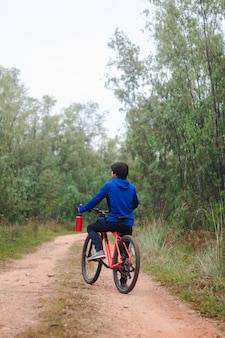Young man on his bike on a forest road, playing sports in nature.