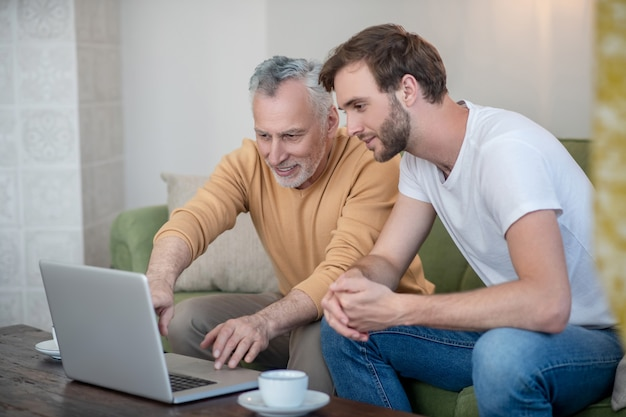 Young man and his dad watching something online and looking involved