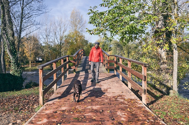 Young man and his dog crossing a bridge on a cold autumn morning.