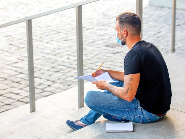 Young man do his homework on the steps of the university campus