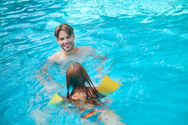 A young man and his kid swimming in the pool and looking enjoyed