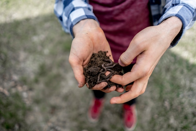 若い男はミミズと土の束を保持します。