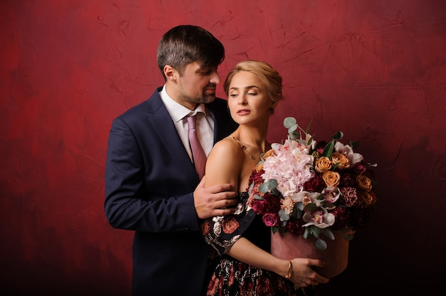 Young man hold his woman on the shoulder with the bouquet of flowers