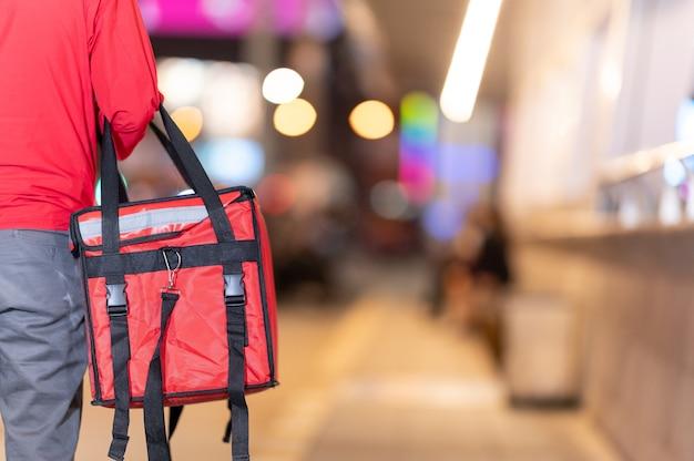 음식 배달을 위해 일하는 큰 빨간 가방에 젊은 남자 보류