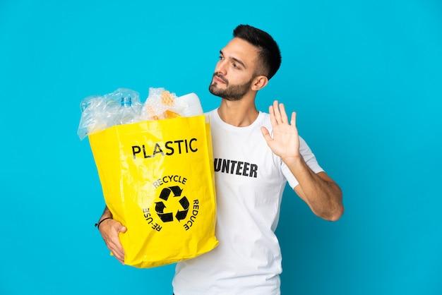 青い壁に隔離されたリサイクルのためにペットボトルでいっぱいのバッグを持っている若い男は、停止ジェスチャーと失望