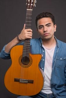 Молодой человек держит красивую гитару на черном фоне. фото высокого качества