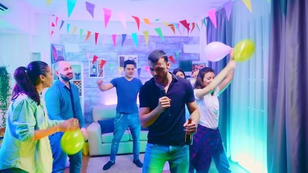 Молодой человек держит бутылку пива на вечеринке и поет караоке. группа людей, танцующих на дикой вечеринке колледжа с неоновыми огнями.