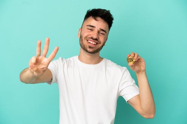 幸せな青い背景に分離されたビットコインを保持し、指で3を数える若い男