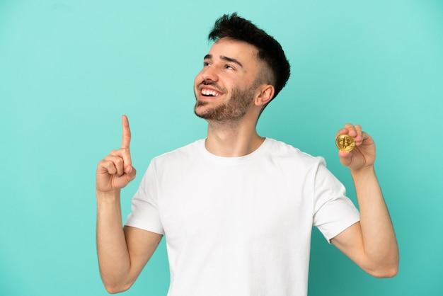 Молодой человек держит биткойн на синем фоне, указывая на отличную идею