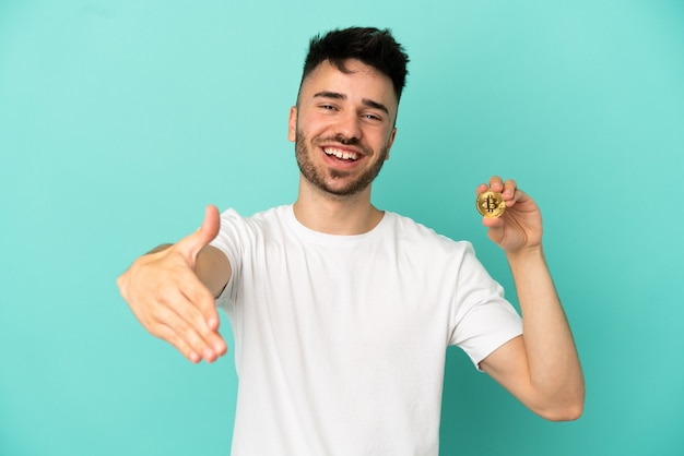 Молодой человек, держащий биткойн на синем фоне, пожимая руку для заключения хорошей сделки