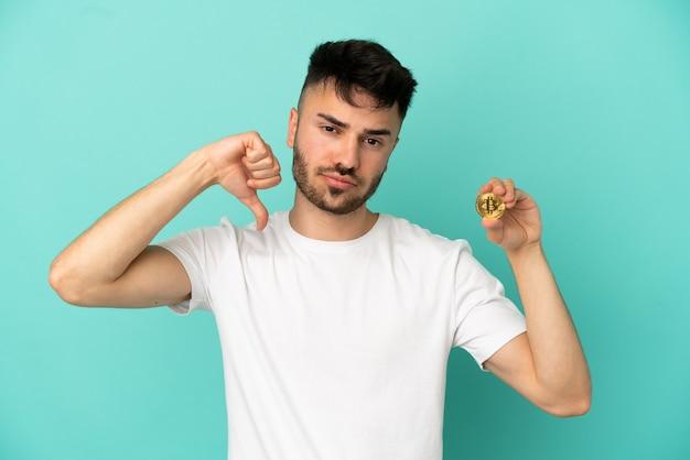Молодой человек, держащий биткойн, изолированный на синем фоне, показывает большой палец вниз с отрицательным выражением лица