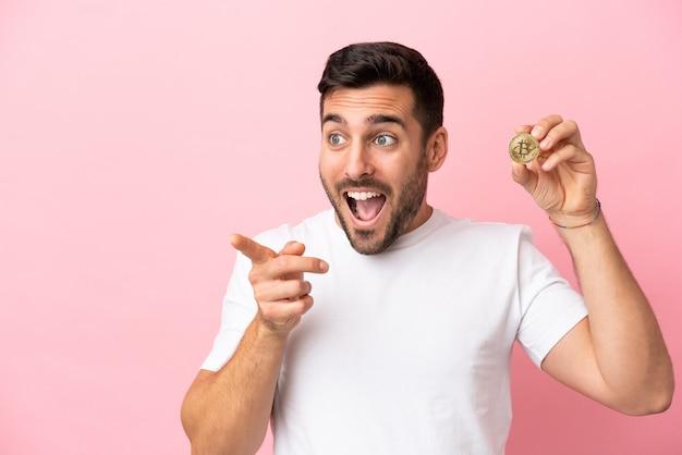 Молодой человек держит биткойн на розовом фоне, указывая пальцем в сторону и представляет продукт