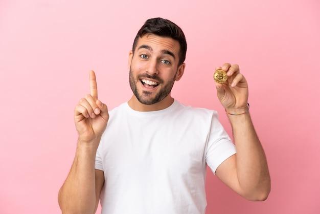 Молодой человек, держащий биткойн на розовом фоне, показывает и поднимает палец в знак лучших